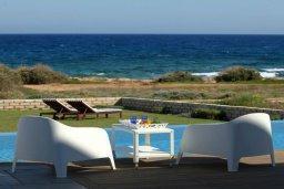 Зона отдыха у бассейна. Кипр, Пернера : Уникальная и современная вилла в греческом стиле с панорамным видом на Средиземное море, с 5-ю спальнями, с бассейном, тенистой террасой с патио и барбекю, расположенная на побережье около пляжа Crystal Springs Beach