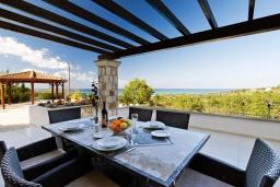 Обеденная зона. Кипр, Помос : Роскошная вилла с террасой на крыше с панорамным видом на море, с 5-ю спальнями, с пейзажным бассейном, джакузи и lounge-зоной, расположена в горах Ayia Marina