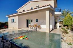 Фасад дома. Кипр, Пейя : Шикарная солнечная вилла с 4-мя спальнями, 4-мя ванными комнатами, 2-мя гостиными, с бассейном, детской площадкой, настольным теннисом, тенистой террасой с патио и барбекю, расположена в красивой деревне Peyia