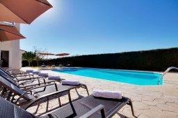 Зона отдыха у бассейна. Кипр, Пейя : Шикарная солнечная вилла с 4-мя спальнями, 4-мя ванными комнатами, 2-мя гостиными, с бассейном, детской площадкой, настольным теннисом, тенистой террасой с патио и барбекю, расположена в красивой деревне Peyia