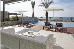 Зона отдыха у бассейна. Кипр, Аммос - Лимнария Бич : Элегантная вилла на побережье с панорамным видом на Средиземное море, с 6-спальнями, пейзажным бассейном, сауной, солнечной террасой на крыше с джакузи, расположена в 50 метрах от уединенной песчаной бухты