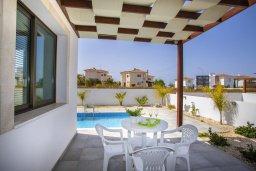Зона отдыха у бассейна. Кипр, Пернера Тринити : Прекрасная вилла с 4-мя спальнями, 3-мя ванными комнатами, бассейном, тенистой террасой с патио и каменным барбекю, расположена недалеко от пляжа Aiyialos Beach