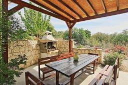 Обеденная зона. Кипр, Полис город : Впечатляющая каменная вилла с 5-ю спальнями, 4-мя ванными комнатами, бассейном, в окружение пышного зелёного сада, беседкой с патио и каменным барбекю, и детской площадкой,  расположена в Goudi