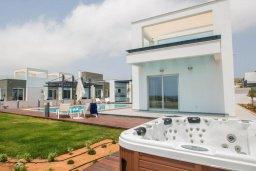 Зона отдыха у бассейна. Кипр, Аммос - Лимнария Бич : Современная шикарная вилла на берегу моря с 6-ю спальнями, 4-мя ванными комнатами, с большим бассейном, джакузи, тенистой террасой с lounge-зоной, уличным баром, барбекю, сауной, тренажерным залом и садом на крыше с потрясающим видом на Средиземное море