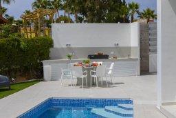 Зона отдыха у бассейна. Кипр, Каво Марис Протарас : Роскошная современная вилла с 3-мя спальнями, 3-мя ванными комнатами, бассейном, зелёным двориком с патио и барбекю, расположена в 100 метрах от пляжа Vyzakia Beach