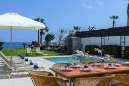 Обеденная зона. Кипр, Каппарис : Роскошная современная вилла с панорамным видом на море, с 5-ю спальнями, 4-мя ванными комнатами, бассейном, садом с зелёной лужайкой, патио и каменным барбекю, расположена на берегу моря  в закрытом комплексе в тихом районе Каппарис