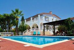 Фасад дома. Кипр, Киссонерга : Прекрасная вилла с бассейном, зеленым двориком с барбекю и детской площадкой, 6 спален, 4 ванные комнаты, парковка, Wi-Fi
