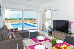Гостиная. Кипр, Ионион - Айя Текла : Великолепная и современная вилла с панорамным видом на Средиземное море, с 3-мя спальнями, 2-мя ванными комнатами, с бассейном, солнечной террасой с патио, уличным баром и барбекю, расположена в прибрежной зоне Ayia Thekla