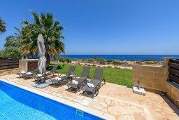Зона отдыха у бассейна. Кипр, Коннос Бэй : Шикарная вилла с панорамным видом на Средиземное море, с 3-мя спальнями, 3-мя ванными комнатами, с бассейном, тенистой террасой с патио, барбекю и lounge-зоной, расположена в тихом и закрытом жилом комплексе недалеко от пляжа Konnos Beach