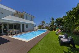 Фасад дома. Кипр, Перволия : Современная вилла с 4-мя спальнями, 3-мя ванными комнатами, с бассейном, в окружении пышного зелёного сада, с тенистой террасой с патио и барбекю, расположена в тихом районе Kiti