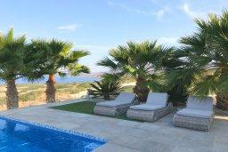 Зона отдыха у бассейна. Кипр, Св.Георг : Шикарная вилла с панорамным видом на Средиземное море, с 4-мя спальнями, с пейзажным бассейном, тенистой террасой с патио и традиционным кипрским барбекю, расположена недалеко от пляжа White River Beach