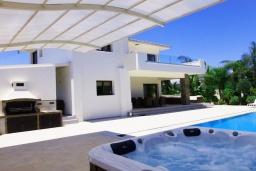 Развлечения и отдых на вилле. Кипр, Коннос Бэй : Роскошная вилла с 4-мя спальнями, с бассейном, джакузи, солнечной террасой с lounge-зоной, дровяной кипрской печью, в окружении пышного зелёного сада, с тренажерным залом и сауной, расположена в 500 метрах от пляжа Konnos Bay Beach