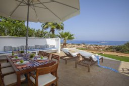 Обеденная зона. Кипр, Коннос Бэй : Современная вилла с шикарным видом на море, с 5-ю спальнями, с lounge-зоной и барбекю, расположена на первой линии