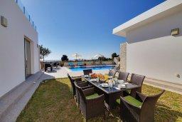 Обеденная зона. Кипр, Корал Бэй : Роскошная вилла с 5-ю спальнями, с видом на море, с бассейном, детской площадкой и зелёной территорией с патио и барбекю