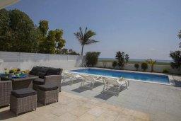 Зона отдыха у бассейна. Кипр, Мазотос : Прекрасная вилла с потрясающим видом на море, с 4-мя спальнями, с бассейном, уютным патио, расположена всего в нескольких шагах от пляжа