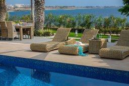 Зона отдыха у бассейна. Кипр, Хлорака : Роскошная вилла в 100 метрах от пляжа с бассейном и зеленым двориком с барбекю, 4 спальни, 3 ванные комнаты, парковка, Wi-Fi